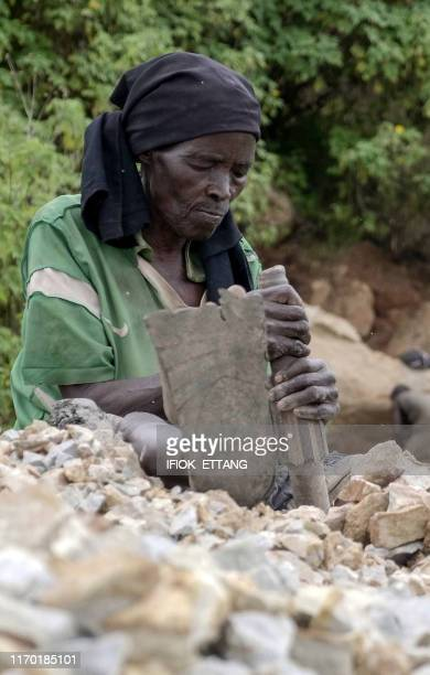 Ninety fouryearold grand mother Azumi Atang sits on ground to break stones with a hammer to make a living in Jos Plateau State in central Nigeria on...