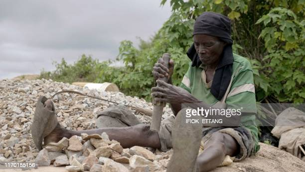 TOPSHOT Ninety fouryearold grand mother Azumi Atang sits on ground to break stones with hammer to make a living in Jos Plateau State in central...
