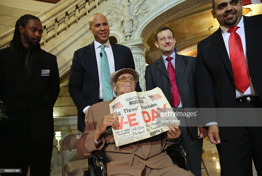 Ninety year-old WWII veteran Willie Wilkins shows a newspaper while standing with Newark Mayor Cory Booker on the 68th Victory in Europe Day at the Newark City Hall on May 8, 2013 in Newark, New Jersey. Booker, who has declared that he will run for New Jersey's open U.S. Senate seat in 2014, honored Wilkins on the 68th anniversary of Victory in Europe Day. At the ceremony, Wilkins was returned his dog tags, which were recently unearthed in a French garden, some 67 years after he lost them in France during WWII.