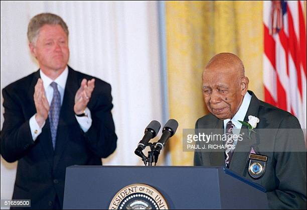 Ninetyfouryearold Herman Shaw speaks as US President Bill Clinton looks on during ceremonies at the White House in Washington 16 May in which Clinton...