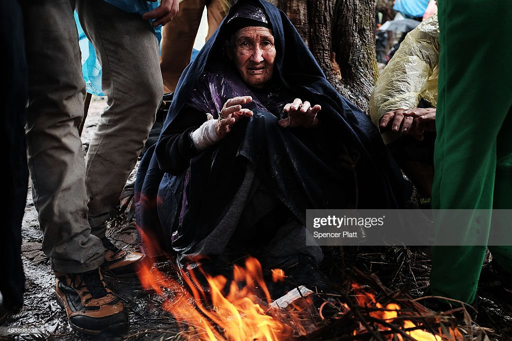 Ninety-year old Bakhtavar Nazary of Bamiyan, Afghanistan warms herself by a fire at the increasingly overwhelmed Moria camp on the island of Lesbos on October 23, 2015 in Mitilini, Greece. Dozens of rafts and boats are still making the journey daily as thousands flee conflict in Iraq, Syria, Afghanistan and other countries. More than 500,000 migrants have entered Europe so far this year. Of that number four-fifths of have paid to be smuggled by sea to Greece from Turkey, the main transit route into the EU. Nearly all of those entering Greece on a boat from Turkey are from the war zones of Syria, Iraq and Afghanistan.