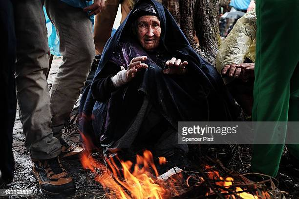 Ninetyyear old Bakhtavar Nazary of Bamiyan Afghanistan warms herself by a fire at the increasingly overwhelmed Moria camp on the island of Lesbos on...