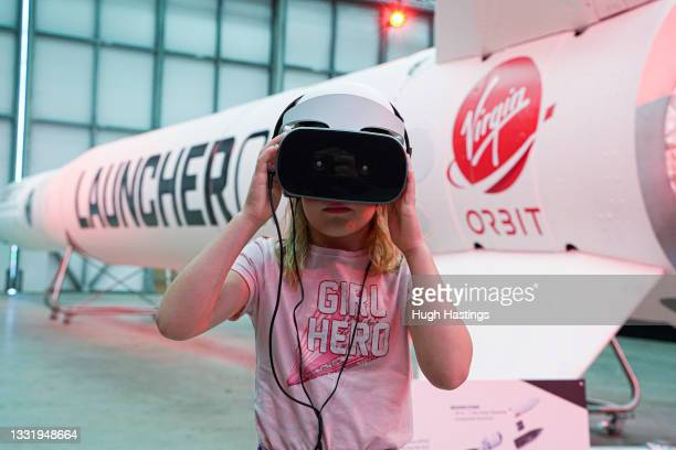 Nine-year old Lottie uses a VR unit in front of the Virgin Orbit Launcher One rocket on the opening day of the Story of a Satellite summer exhibition...