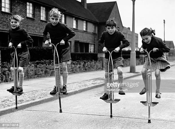 Nineyear old quadruplets Robert Paul Kevin and Annete Taylor enjoy playing with their new pogo sticks in Edmonton London England