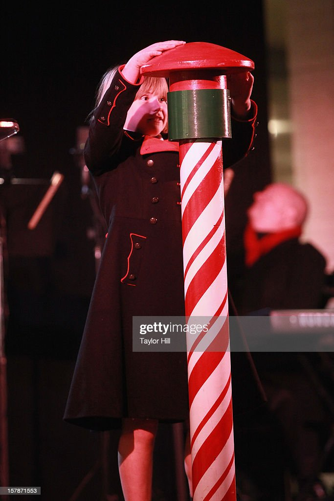 Nine-year-old Abigail Simmons hits the button that lights the tree at The Metropolitan Opera Tree Lighting Ceremony at The Metropolitan Opera House on December 6, 2012 in New York City.