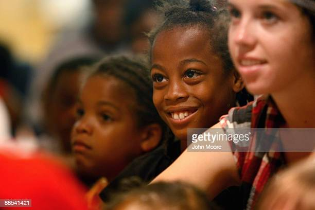 Nine-year-old Coulet Johnson , sits with fellow homeless children while watching circus clowns at a free performance at the Dallas Public Library on...