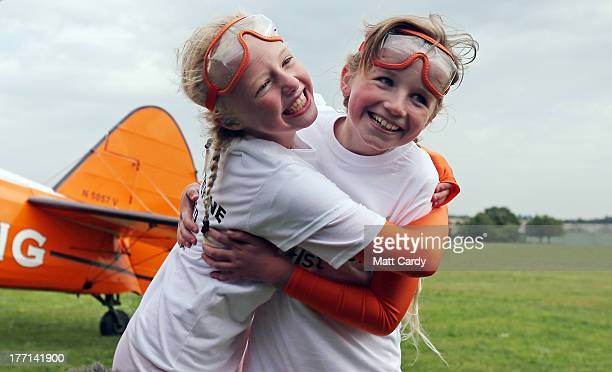 Nineyearold cousins Rose Brewer and Flame Brewer hug each other after they completed their wingwalk over Rendcomb airfield in Gloucestershire to...