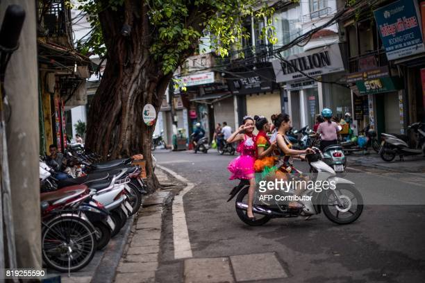 A nineyearold girl strikes a pose as she and her friend are driven to school on a moped by their mother in Hanoi on July 20 2017 The girls were...
