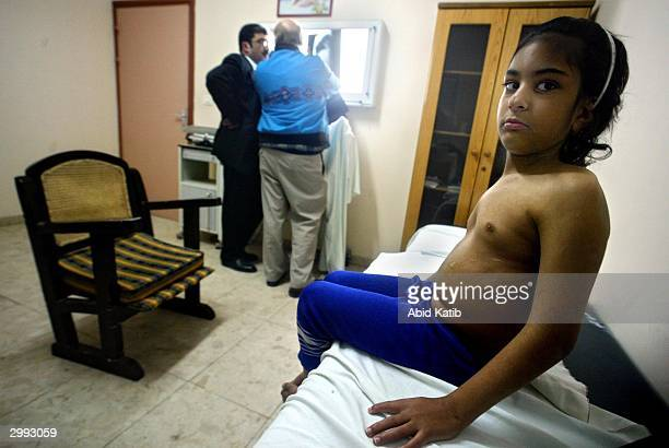 Nineyearold Palestinian girl Sabrein Mashharawi who is suffering from scoliosis looks on as she is treated by US pediatric orthopedic surgeon Hugh...