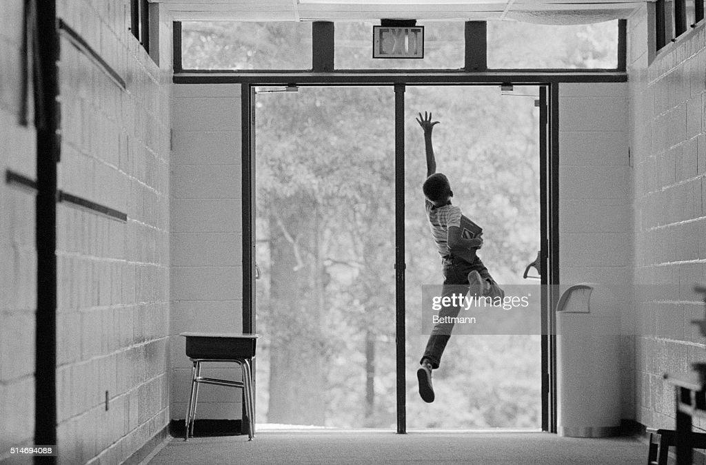 Boy Jumping in Doorway : News Photo