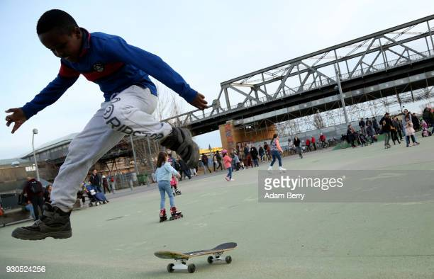 Nineyearold William jumps off his skateboard in a park on March 11 2018 in Berlin Germany A high temperature of 16 degrees Celsius brought residents...