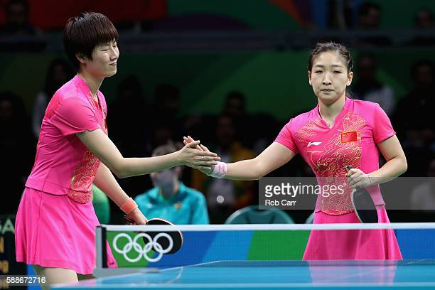 Ning Ding and Liu Shiwen of China celebrate after defeating Brazil during the Women's Team Round 1 on Day 7 of the Rio 2016 Olympic Games at...