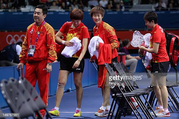 Ning Ding Xiaoxia Li and Yue Guo of China leave with their coach Zhihao Shi during Women's Team Table Tennis first round match against team of Spain...