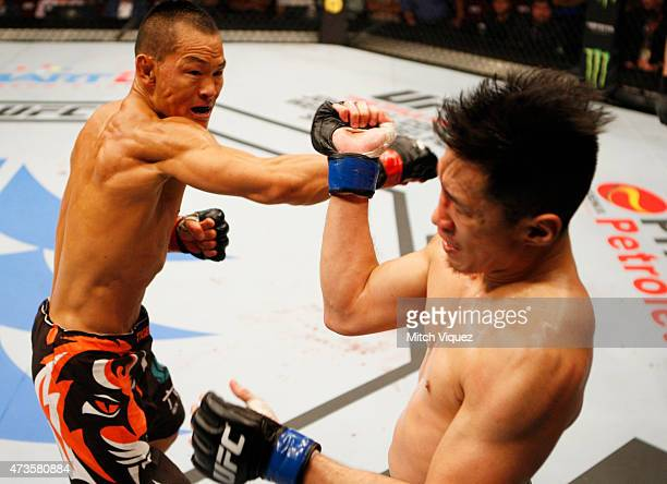 Ning Guangyou of China throws a punch at Royston Wee of Singapore in their bantamweight fight during the UFC Fight Night event at the Mall of Asia...