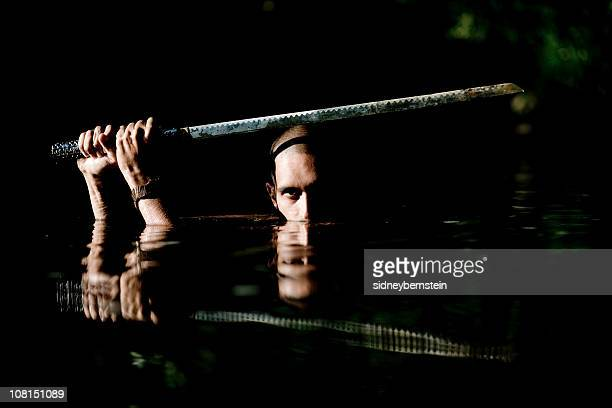 Ninja Holding Sword Above Head and Wading Through Water