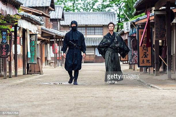 ninja, samurai walk in the middle of a village street - guerrilla warfare stock pictures, royalty-free photos & images
