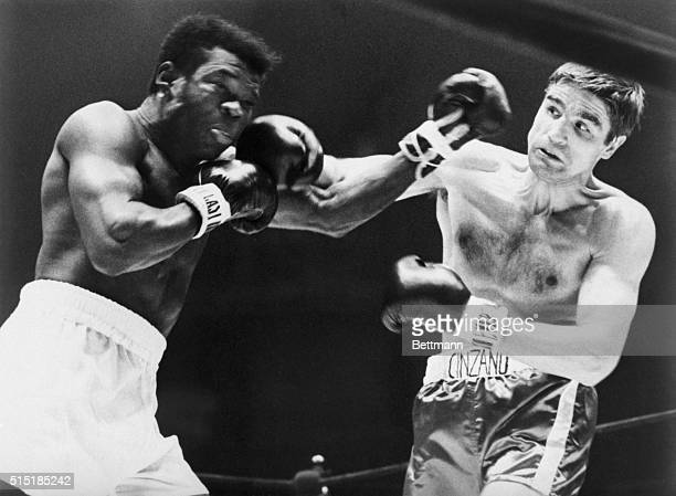 Nino Benvenuti is tensed up as he delivers a right to the jaw of Emile Griffith during their 1968 title bout. Nino challenged and won the crown.