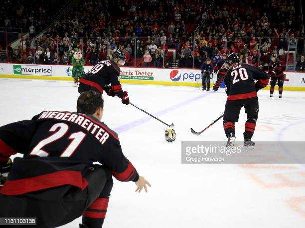 Nino Niederreiter of the Carolina Hurricanes participates in the Storm Surge with teammates Sebastian Aho and Dougie Hamiilton following a victory...