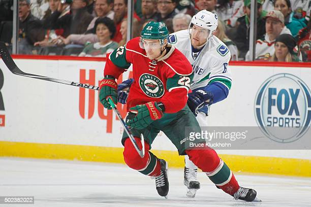 Nino Niederreiter of the Minnesota Wild skates to the puck with Yannick Weber of the Vancouver Canucks defending during the game on December 15 2015...