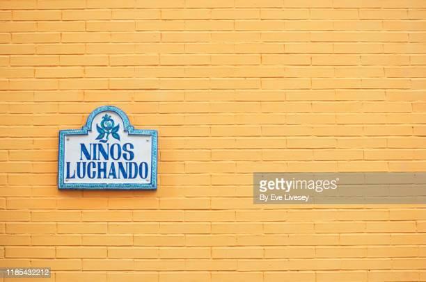ninos luchando (fighting children) ceramic street name sign - andalucia fotografías e imágenes de stock