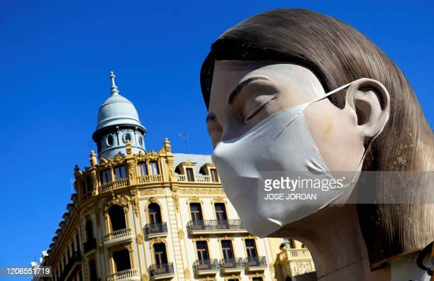 A ninot a gigantic structure made of cardboard portraying current events wearing a protective mask is displayed in Valencia on March 11 2020 after...