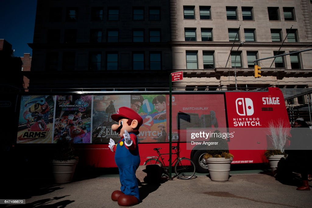 A Nintendo branded bus passes by as a person dressed as the Nintendo character Mario waves at a pop-up Nintendo venue in Madison Square Park, March 3, 2017 in New York City. The Nintendo Switch console goes on sale today and retails for 300 dollars.