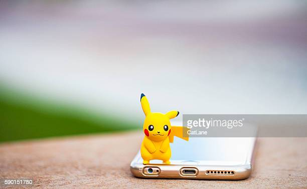 nintendo pokemon go character pikachu and iphone - pikachu stock photos and pictures