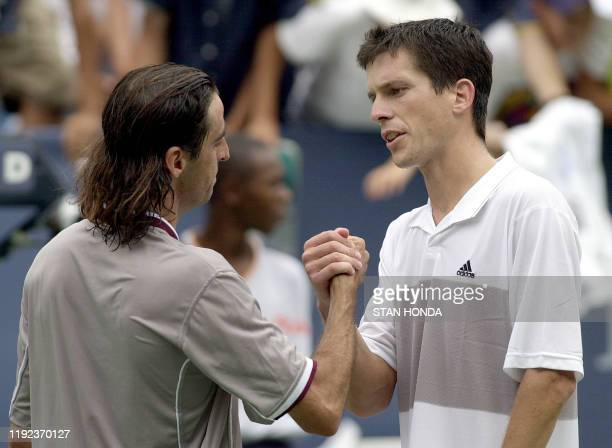 Ninth seed Tim Henman of Great Britain shakes hands with Fernando Meligeni of Brazil after their second round US Open match at Flushing Meadows New...