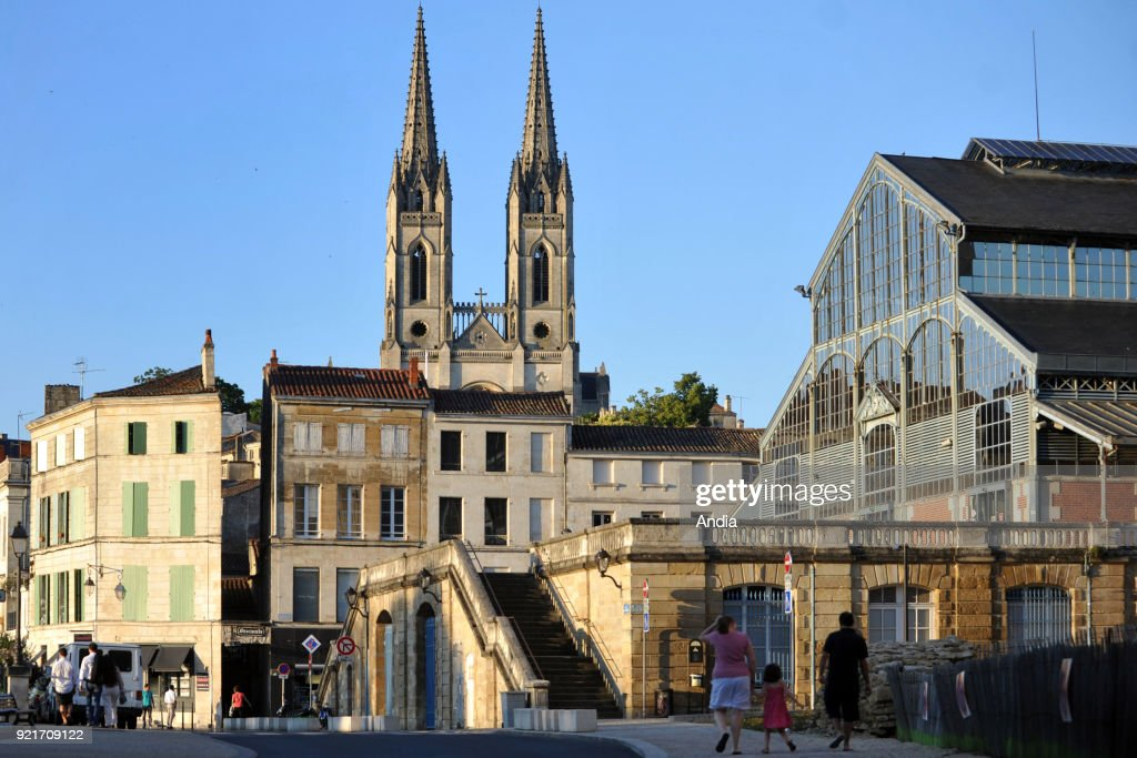 Niort (central-western France). . Properties and central covered market, along Quai Cronstadt, by the Sevre Niortaise river. In the background, spires of the Roman Church of Saint-Andre (St Andrew).