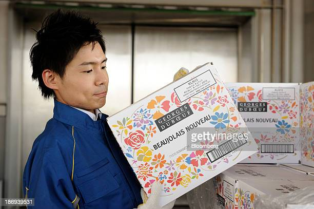 A Nippon Express Co employee carries a box of Beaujolais Nouveau wine at Haneda Airport in Tokyo Japan on Tuesday Nov 5 2013 Japanese appetite for...