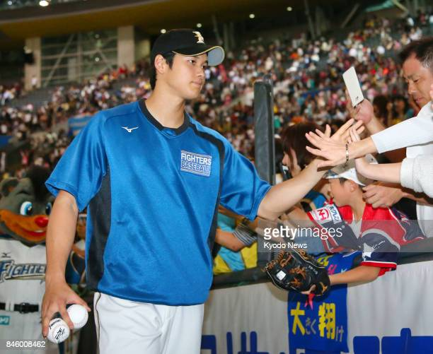 Nippon Ham Fighters pitcher Shohei Otani celebrates with fans after earning his first win of the season against the Rakuten Eagles at Sapporo Dome in...