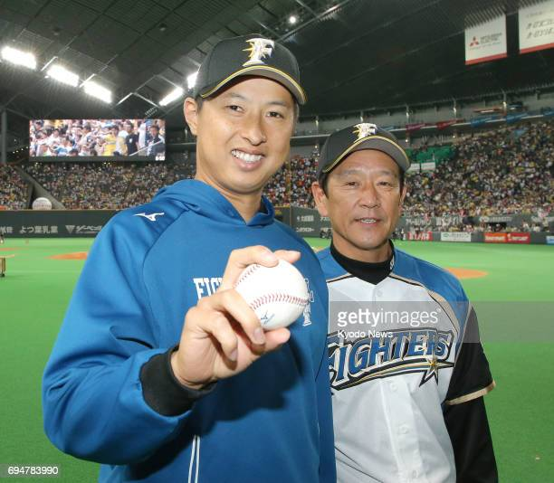 Nippon Ham Fighters' pitcher Toru Murata poses with team manger Hideki Kuriyama after the team's 51 victory over the Yomiuri Giants in Sapporo on...