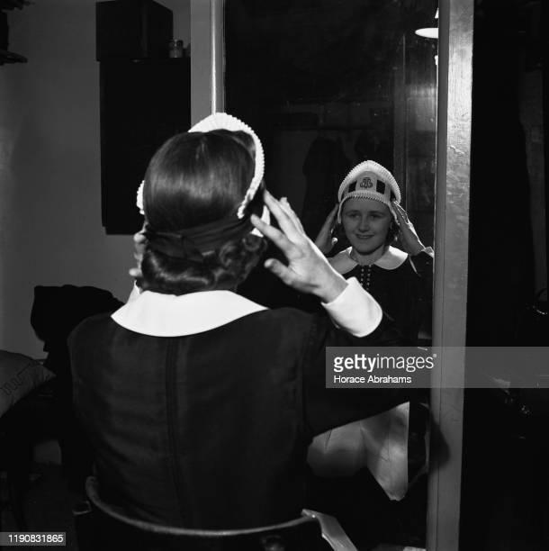 A 'nippy' or waitress at a J Lyons Co tea shop in London getting dressed for work during World War II March 1941