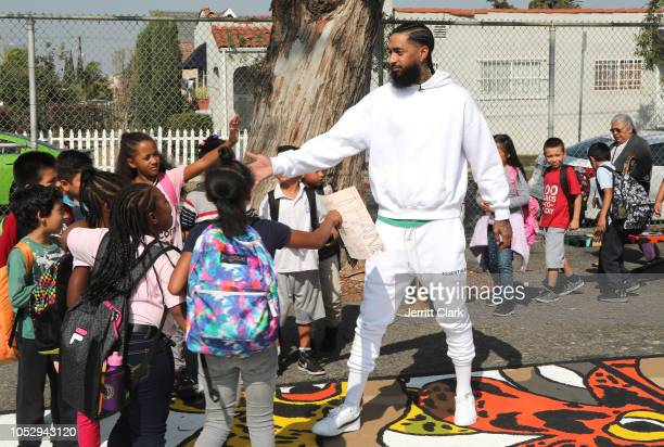 Nipsey Hussle greets kids at the Nipsey Hussle x PUMA Hoops Basketball Court Refurbishment Reveal Event on October 22 2018 in Los Angeles California