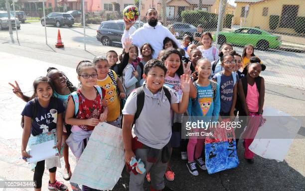 Nipsey Hussle poses with kids at the Nipsey Hussle x PUMA Hoops Basketball Court Refurbishment Reveal Event on October 22 2018 in Los Angeles...