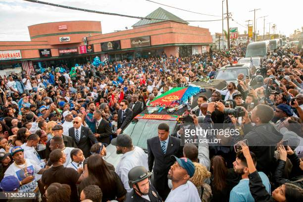 TOPSHOT Nipsey Hussle's procession passes his Marathon Clothing store after his memorial at the Staples Center in Los Angeles California on April 11...