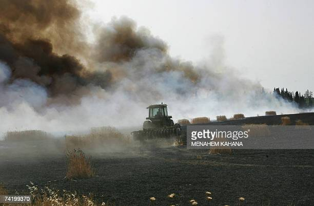 An Israeli farmer uses his tractor in an attempt to control a fire after a 115mm Qassam rocket crashed in a wheat field near the southern Israeli...