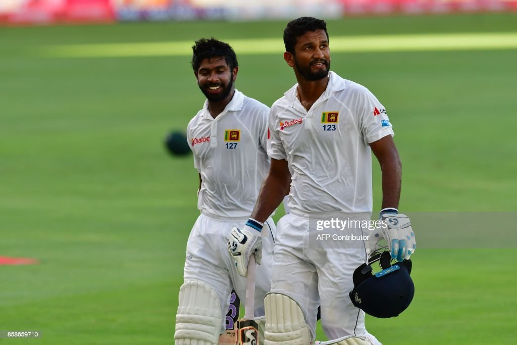 Niroshan Dickwella and Dimuth Karunaratne (R) of Sri Lanka leave the field during the second day of the second Test cricket match between Sri Lanka and Pakistan at Dubai International Stadium in Dubai on October 7, 2017. /