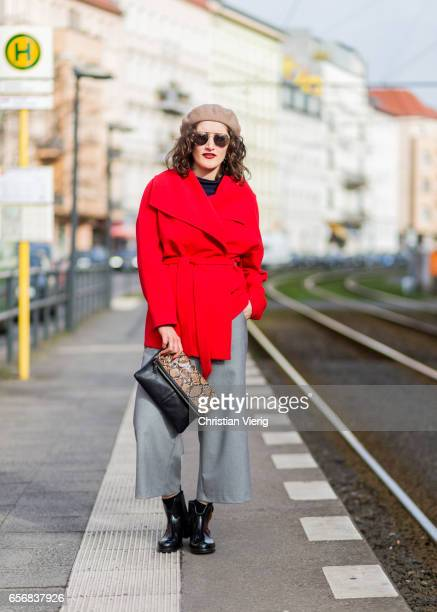 Nisa Aslan wearing a beige beret red wool coat grey wide leg cropped pants leopard print clutch on March 22 2017 in Berlin Germany