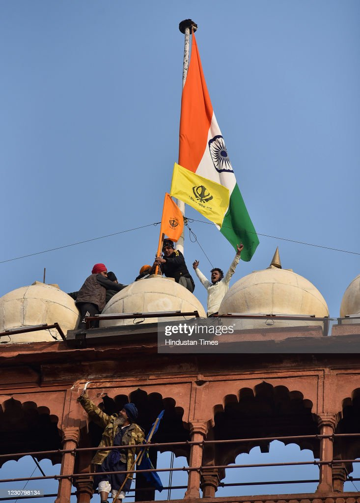 Sikh Religious Flags Hoisted Near The Indian Tricolour At Red Fort During Farmers Tractor Rally : News Photo