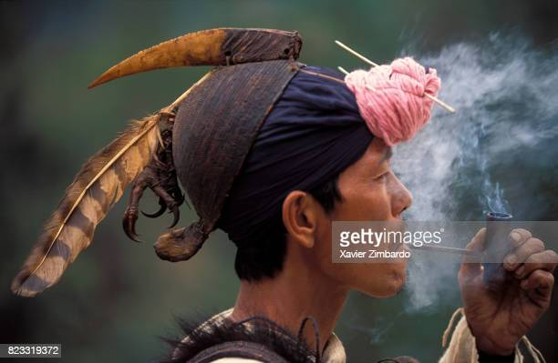 Nishi warrior smoking his pipe wearing a traditional hat decorated with beak and feather of a calao bird on February 13 1996 in Arunachal Pradesh...