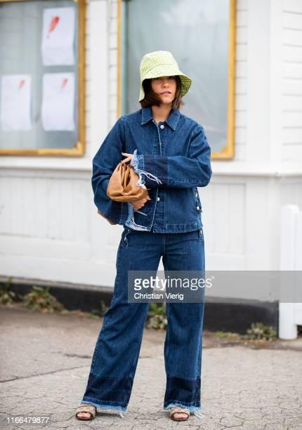 Nisi Kastull is seen wearing denim jacket, jeans, bucket hat, clutch outside Blanche during Copenhagen Fashion Week Spring/Summer 2020 on August 06,...