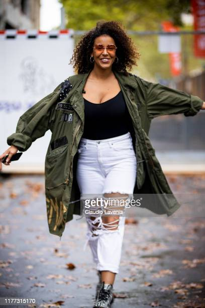Niska Garoute wearing Dust of Gods jacket and white distressed jeans is seen outside the Faith Connexion show during Paris Fashion Week Womenswear...