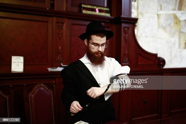 Nissam a member of the Russian Tatarstan's Jewish Lubavitch community removes the Tefillin from his arm at the Kazanskaya synagogue in Kazan on June...
