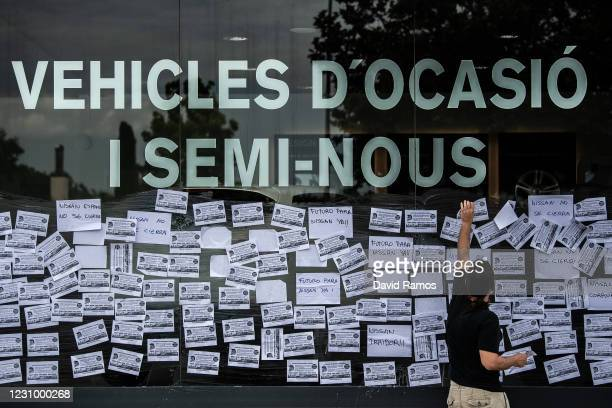 Nissan employee glues banners on a window as he protests outside a Nissan authorized dealer on May 29 2020 in Granollers near Barcelona Spain Nissan...