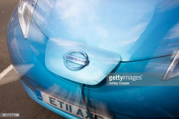 a nissan leaf at a pavement recharging station in london - nissan stock pictures, royalty-free photos & images