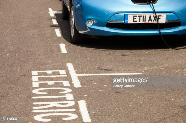 a nissan leaf electric car recharging at a pavement recharging station in london, uk - nissan stock pictures, royalty-free photos & images