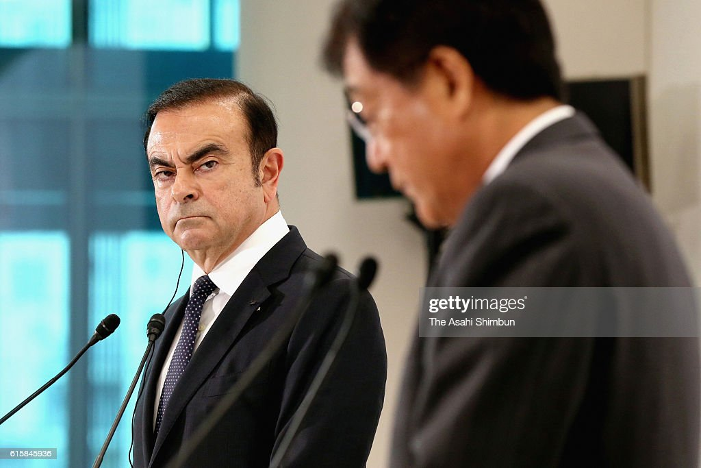 Nissan Motor Co Chairman and CEO Carlos Ghosn wacthes while Mitsubishi Motors Chairman and CEO Osamu Masuko speaks during a press conference on October 20, 2016 in Tokyo, Japan. Nissan acquired 34 percent stake of trouble-prone automaker by paying 2.3 billion U.S. Dollars, becoming the largest shareholder. Ghosn is taking the Chairman's post and Masuko stays as CEO.