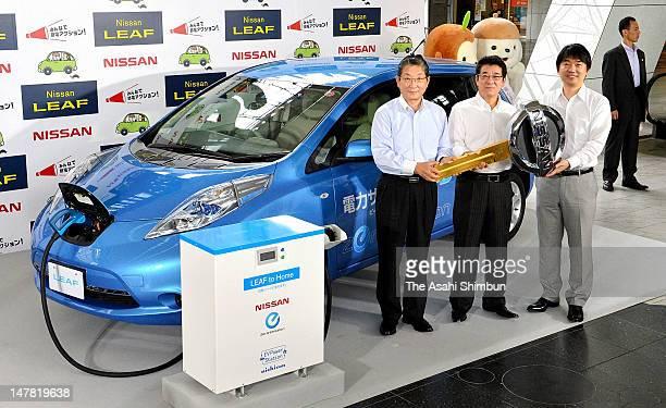 Nissan Motor Co COO Toshiyuki Shiga presents the key to Osaka Prefecture Governor Ichiro Matsui and Osaka City mayor Toru Hashimoto during the...