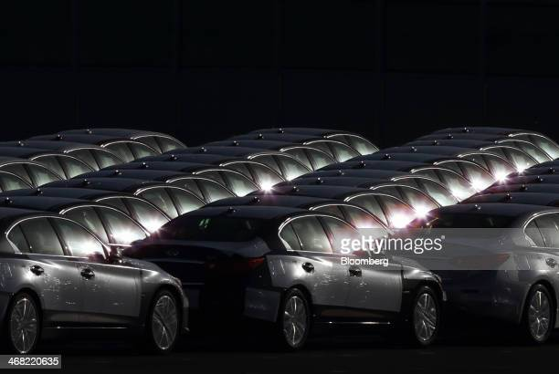 Nissan Motor Co Infiniti branded vehicles bound for shipment sit in a lot at a port in Hitachi City Ibaraki Prefecture Japan on Friday Feb 7 2014...
